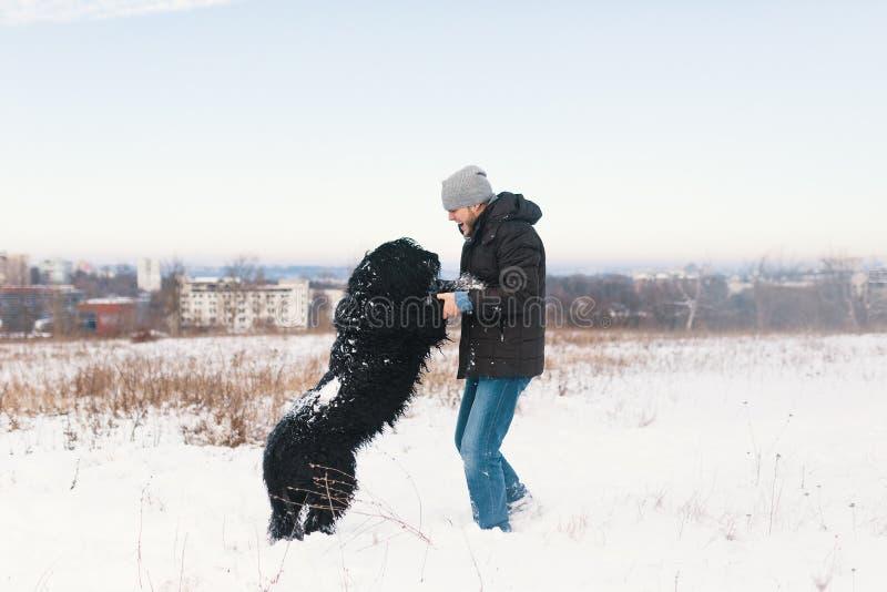 Homem entusiasmado que joga na neve com seu melhor amigo, cão preto imagens de stock royalty free