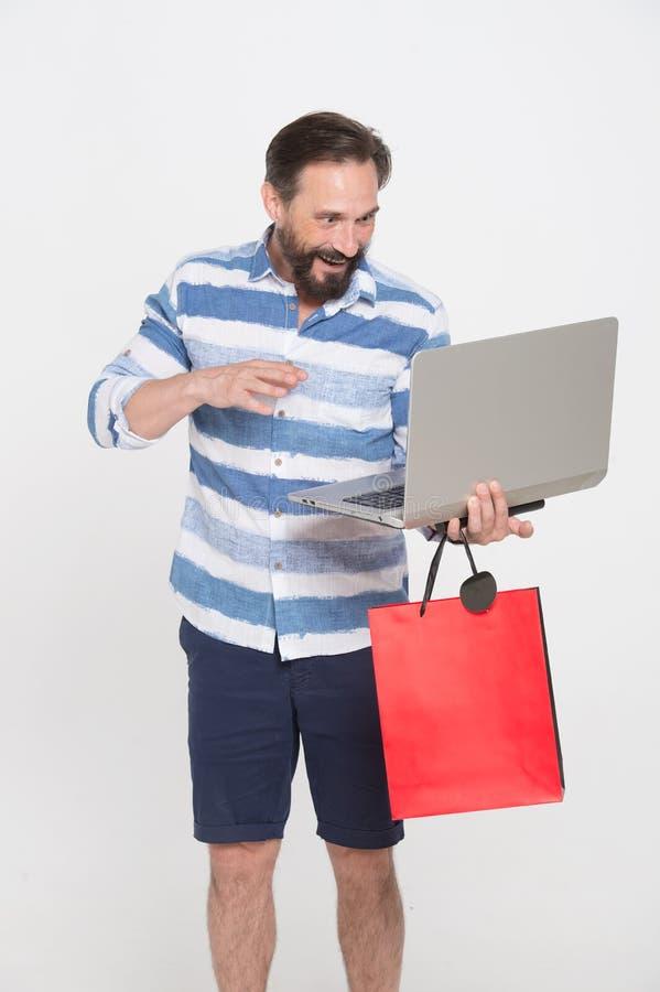 Homem entusiasmado que olha o portátil e que aprecia a compra em linha imagens de stock royalty free
