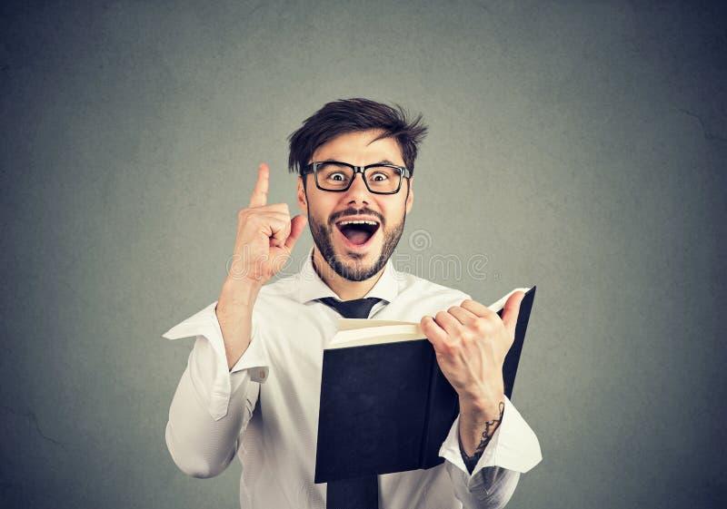 Homem entusiasmado que tem a ideia ao ler um livro fotos de stock