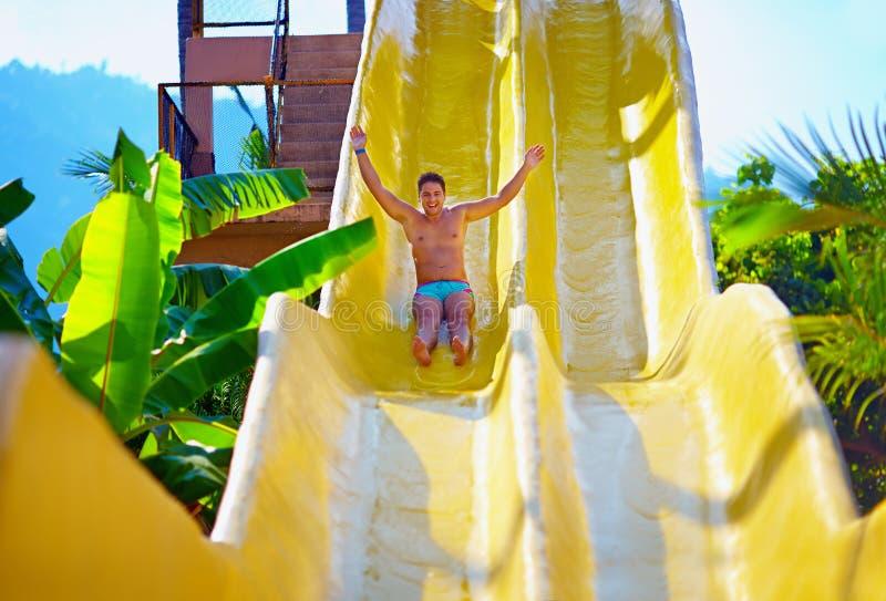 Homem entusiasmado que tem o divertimento na corrediça de água no parque tropical do aqua imagem de stock royalty free