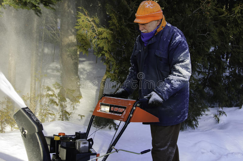 Homem envelhecido atrás de um snowblower fotos de stock royalty free