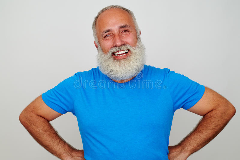 Homem envelhecido considerável que está com mãos nos quadris e no sorriso imagens de stock royalty free