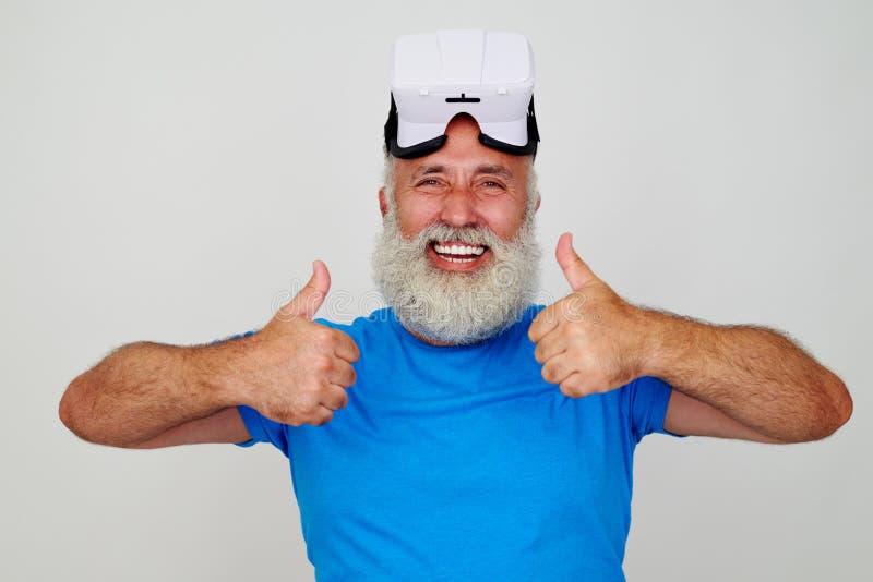 Homem envelhecido de sorriso nos VR-auriculares em sua cabeça que dá dois polegares acima fotos de stock