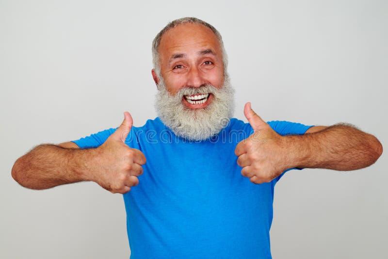 Homem envelhecido de sorriso que dá dois polegares acima contra o fundo branco foto de stock