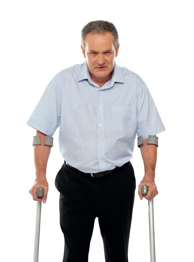 Homem envelhecido irritado com as muletas que olham o fotografia de stock