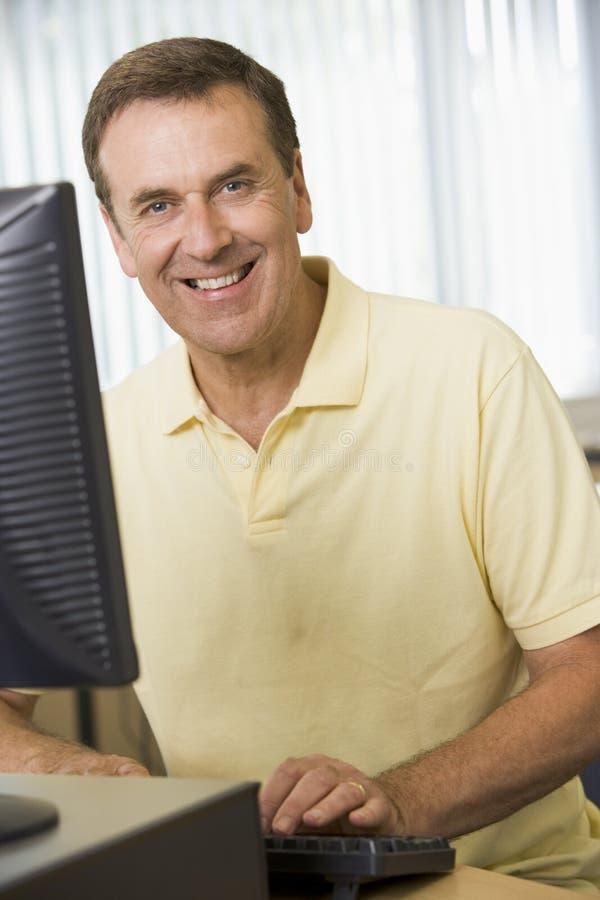 Homem envelhecido médio em um computador fotos de stock