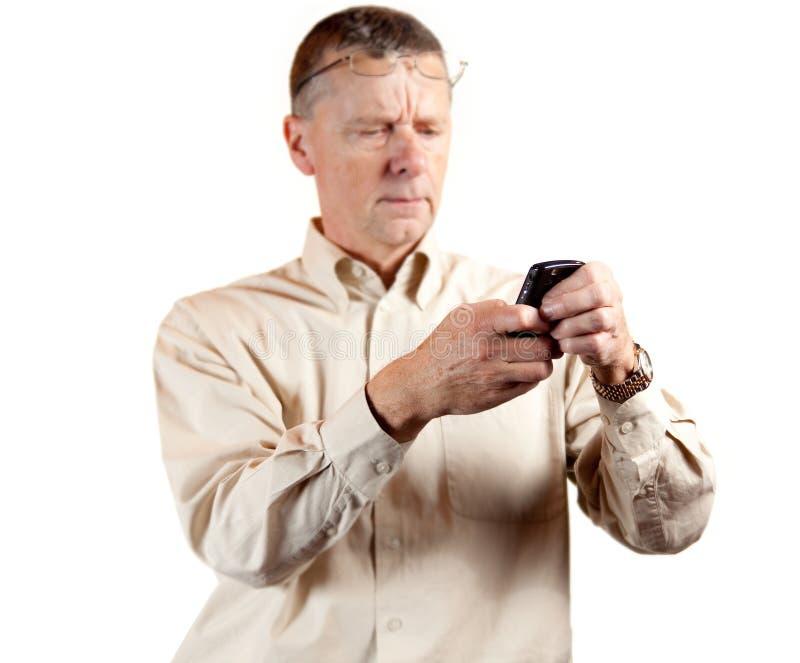 Homem envelhecido médio que é vesgo no telefone esperto imagem de stock