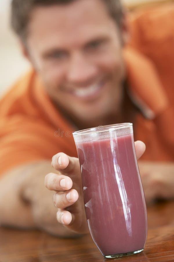Homem envelhecido médio que bebe o Smoothie fresco da baga imagem de stock