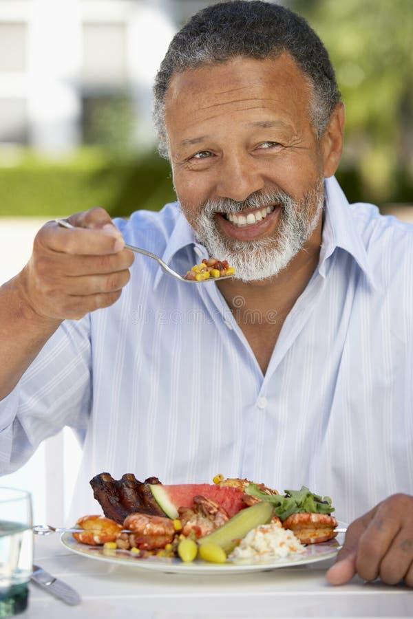 Homem envelhecido médio que janta o fresco do Al imagem de stock