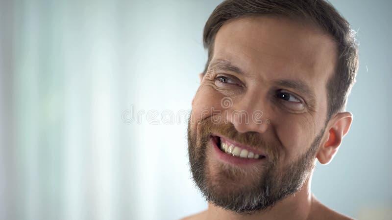 Homem envelhecido médio que verifica os dentes na frente do espelho, doença dental, infecção da goma fotografia de stock