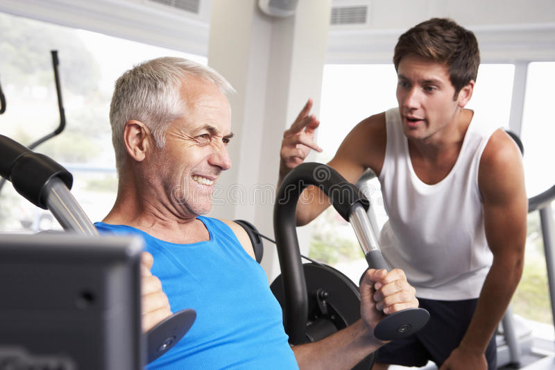 Homem envelhecido meio que está sendo incentivado pelo instrutor pessoal In Gym imagens de stock royalty free