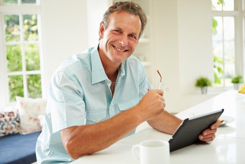 Homem envelhecido meio que usa a tabuleta de Digitas sobre o café da manhã