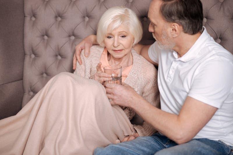 Homem envelhecido que dá o vidro de água à esposa preocupada fotos de stock royalty free