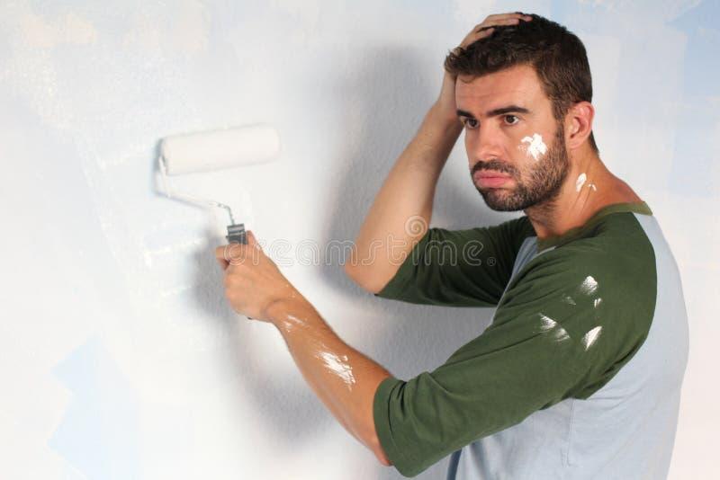 Homem esgotado que tenta pintar uma parede foto de stock