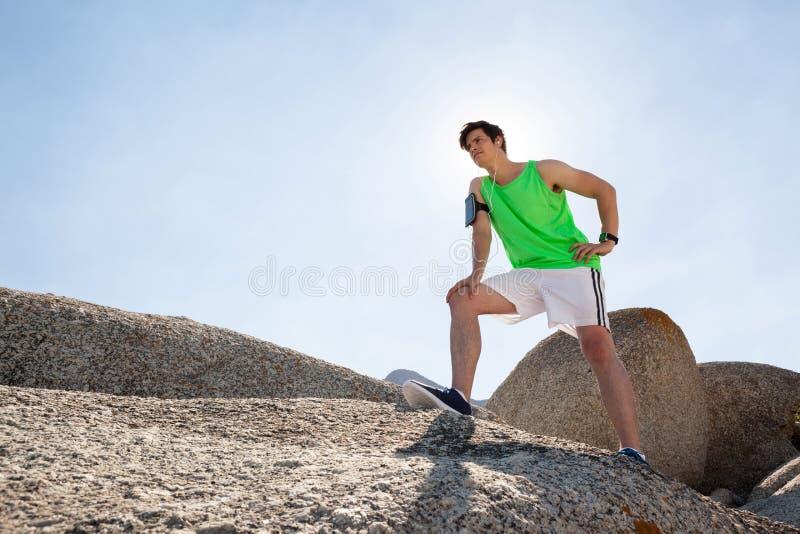 Homem esgotado que toma uma ruptura após movimentar-se na praia fotos de stock