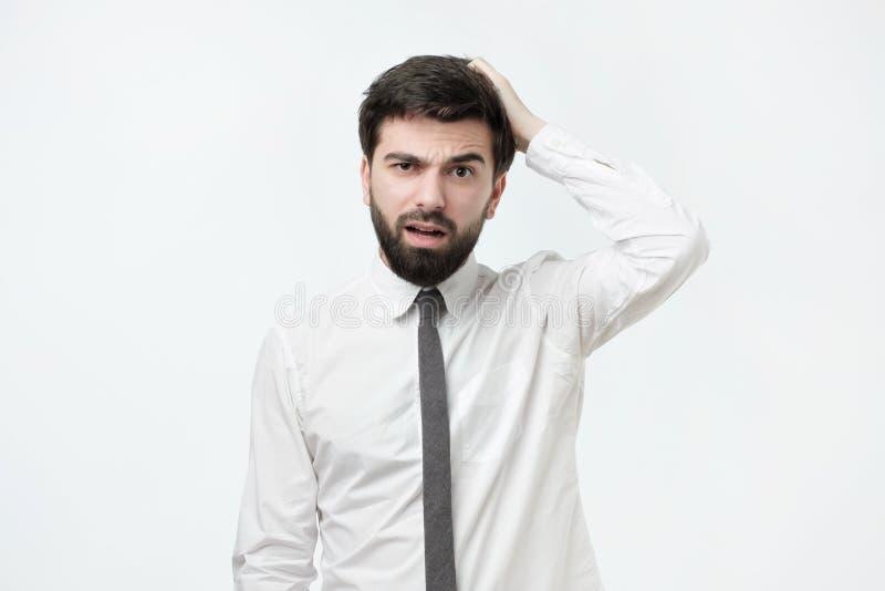 Homem espanhol considerável com a barba que risca a cabeça ao ser confundido ou à nora fotografia de stock
