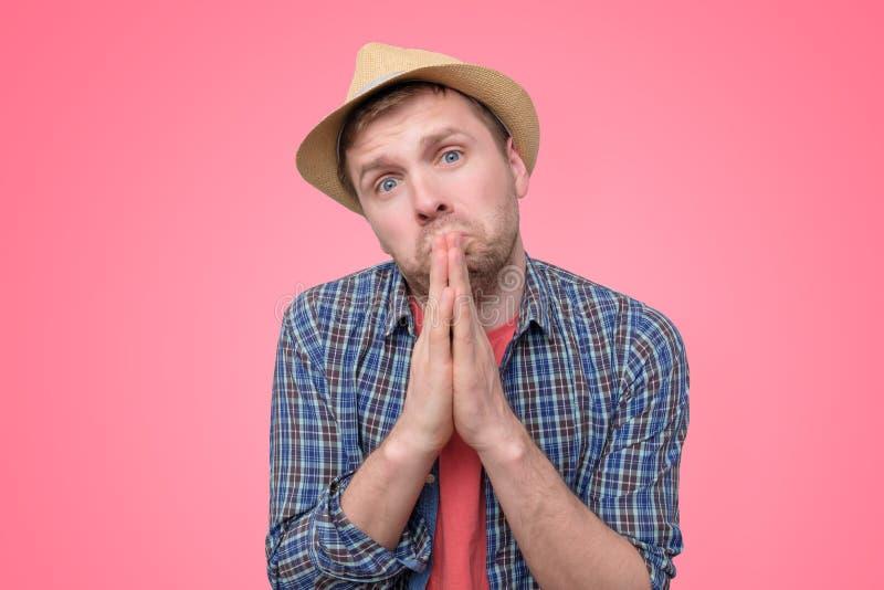 Homem esperançoso no chapéu do verão para juntar-se às mãos na oração que agradece a pedir melhor imagem de stock royalty free