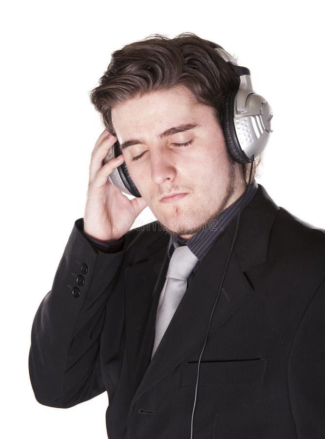 Homem esperta vestido que escuta em auscultadores fotos de stock royalty free
