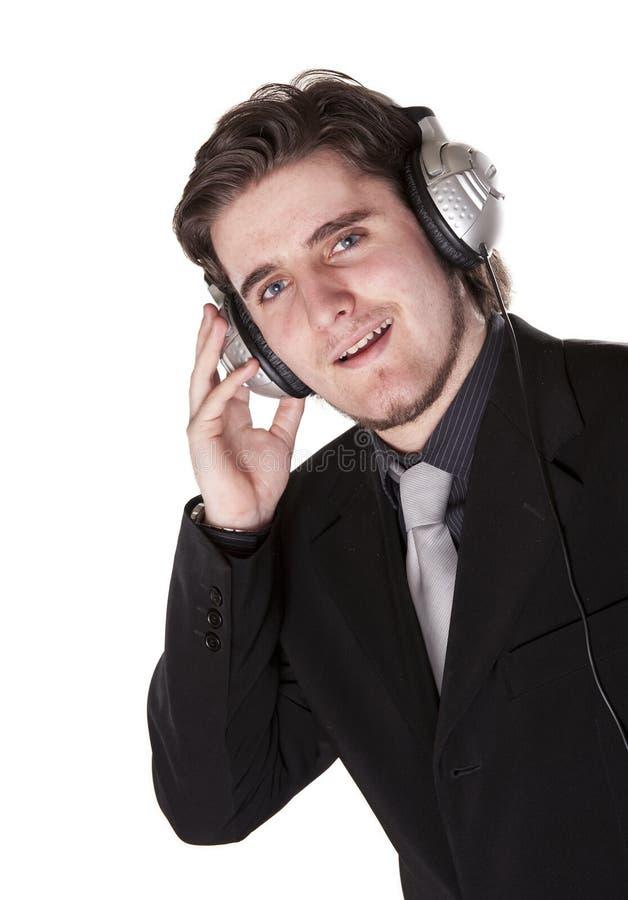 Homem esperta vestido que escuta em auscultadores fotografia de stock royalty free
