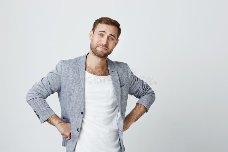 Homem europeu à moda considerável e seguro com a barba no revestimento com o corte de cabelo na moda que guarda as mãos nos quadr imagens de stock
