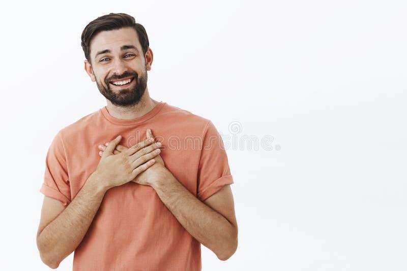 Homem europeu adulto deleitado e grato feliz com a barba no t-shirt cor-de-rosa que guarda as palmas no coração e no sorriso grat fotografia de stock royalty free