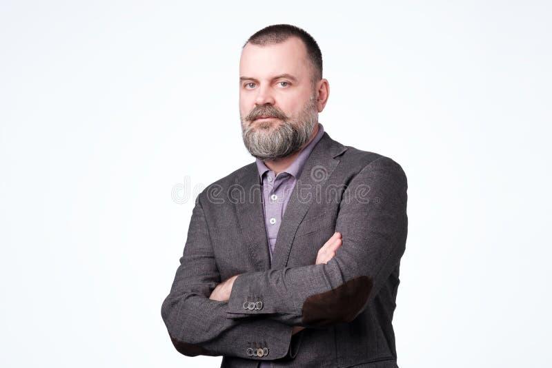Homem europeu maduro sério que olha a câmera com suspeita fotografia de stock royalty free