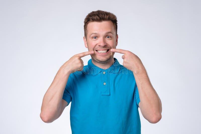 Homem europeu novo em mostras azuis do t-shirt em seus dentes imagens de stock royalty free