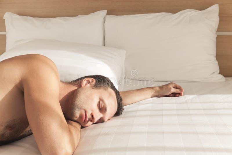 Homem europeu novo que dorme na cama larga imagens de stock royalty free
