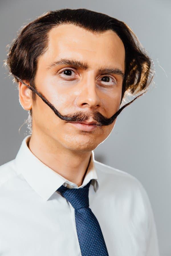 Homem excêntrico com um bigode longo em seus camisa e laço Um trabalhador de escritório louco, um homem de negócios foto de stock royalty free