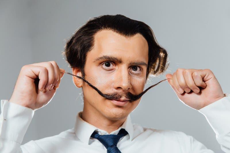 Homem excêntrico com um bigode longo em seus camisa e laço Um trabalhador de escritório louco, um homem de negócios fotografia de stock