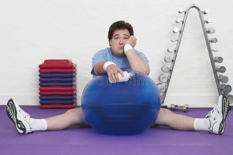Homem excesso de peso no assoalho com bola do exercício fotografia de stock royalty free