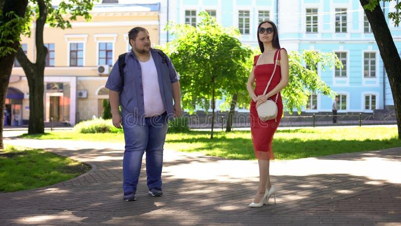 Homem excesso de peso novo que fala à senhora magro no parque, menina bonita que ignora o indivíduo gordo fotografia de stock royalty free