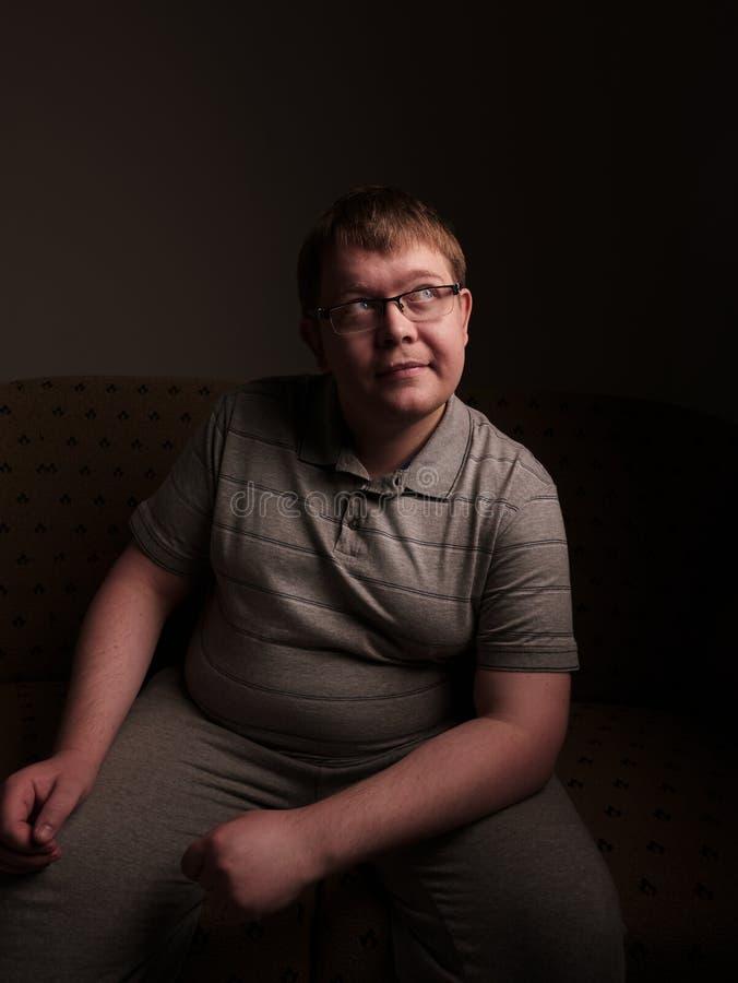 Homem excesso de peso preguiçoso que senta-se no sofá e que olha algo fotografia de stock