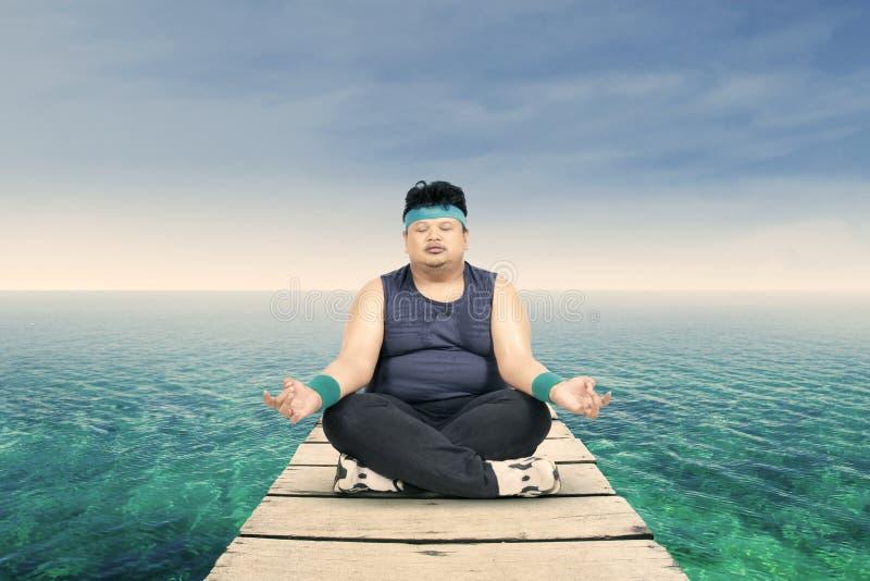 Homem excesso de peso que medita sobre o molhe imagens de stock royalty free
