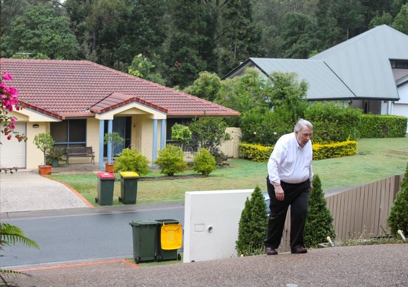 Homem excesso de peso que tem uma dificuldade que anda acima de uma entrada de automóveis extremamente íngreme com as casas da vi imagens de stock