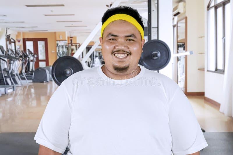Homem excesso de peso de sorriso no centro do gym fotografia de stock