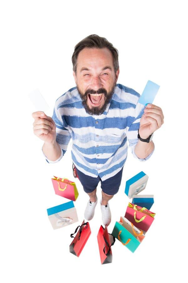 Homem excitado cercado pelas compras que guardam seu cartão do desconto imagens de stock