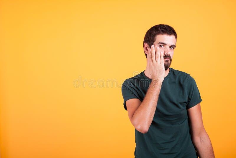 Homem expressivo forçado com suas mãos na cara fotografia de stock