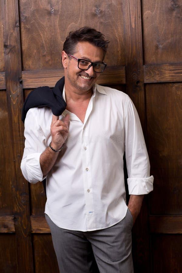 Homem expressivo na camisa branca que olha o e que sorri alegremente imagem de stock