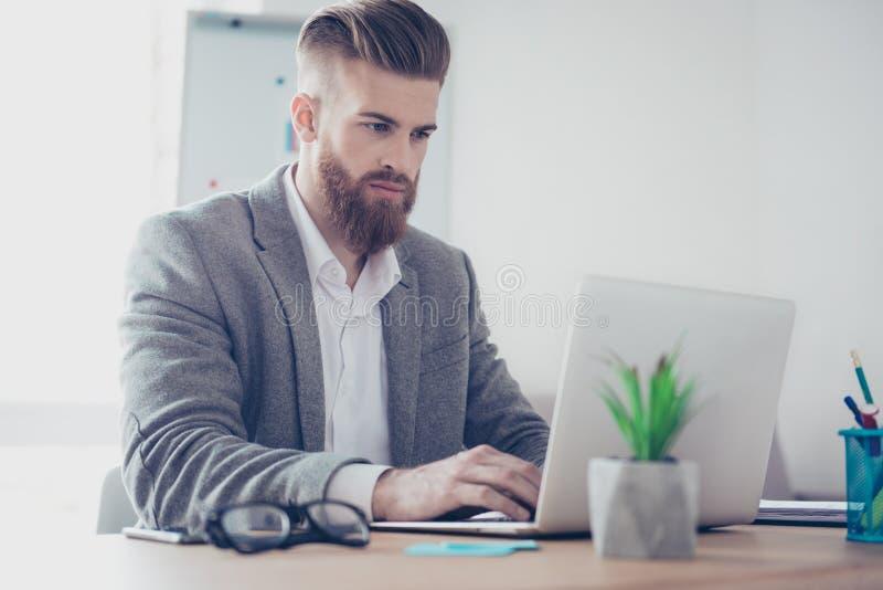 Homem farpado à moda concentrado considerável no revestimento usando seu la foto de stock