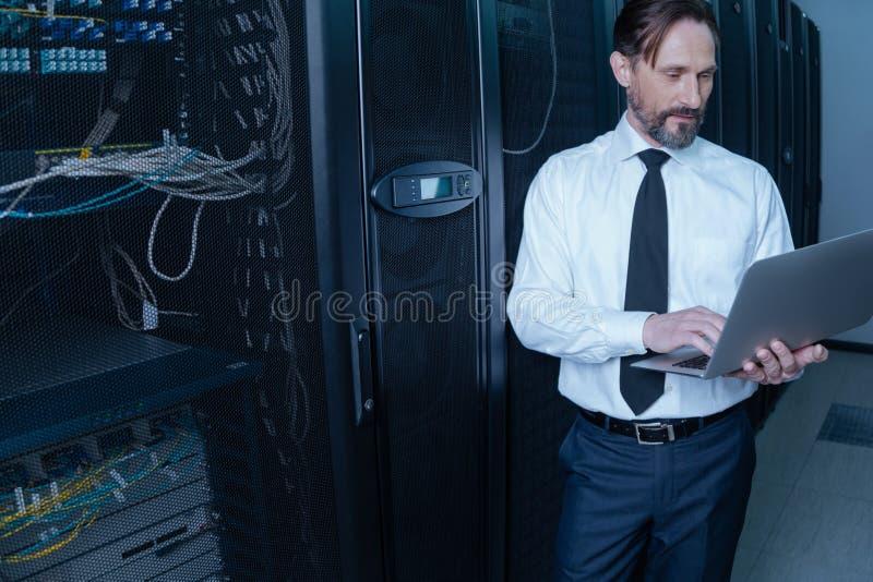 Homem farpado agradável que guarda um portátil fotos de stock