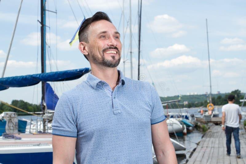 Homem farpado alegre novo do verão que relaxa no veleiro que levanta e que olha distante sobre o fundo do céu dos barcos e das as fotos de stock