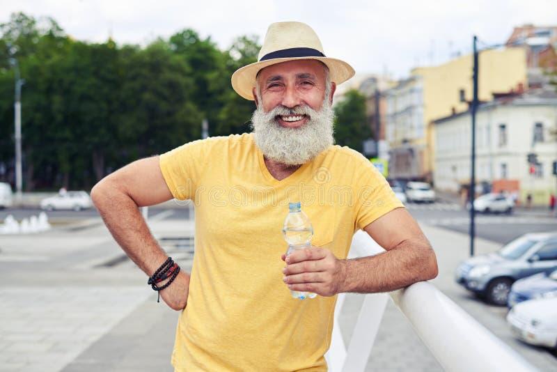 Homem farpado alegre que mantém a garrafa da água contra a arquitetura da cidade imagem de stock