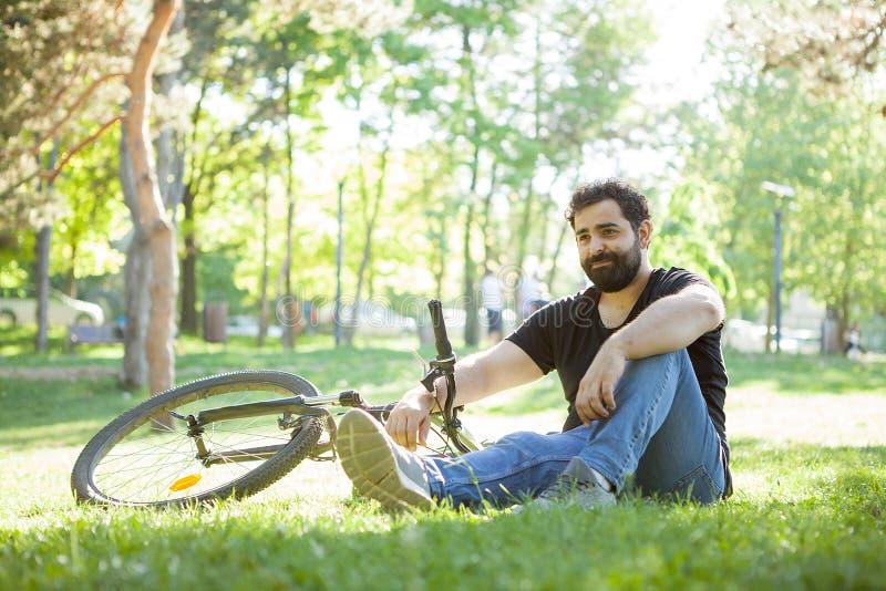 Homem farpado ao lado de sua bicicleta que descansa na terra imagem de stock