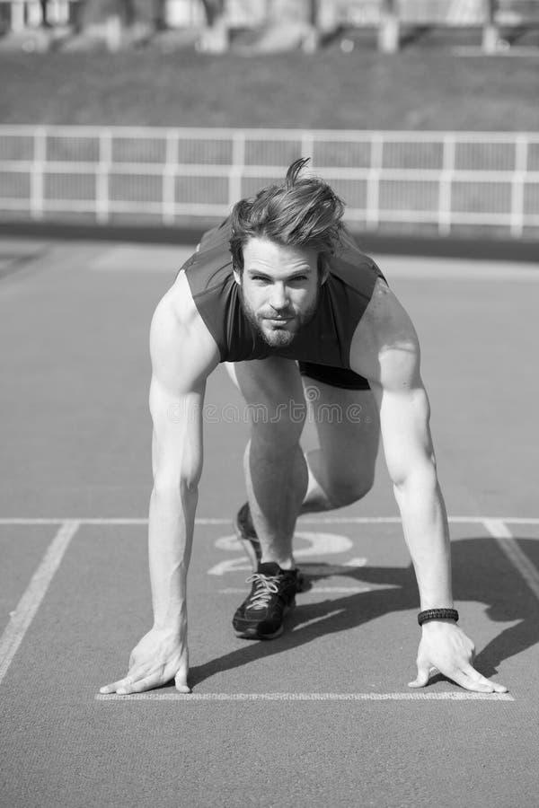 Homem farpado atlético com o corpo muscular que estica em correr o tr fotografia de stock