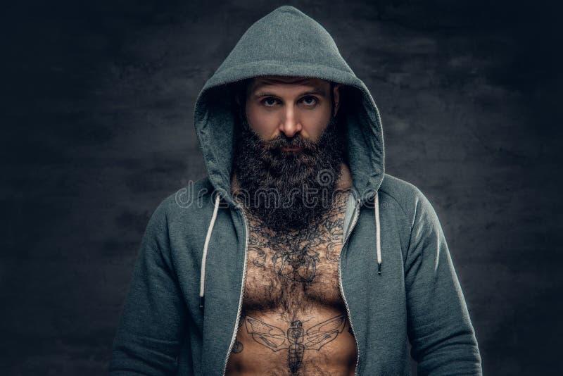Homem farpado atlético em um hoodie cinzento fotos de stock