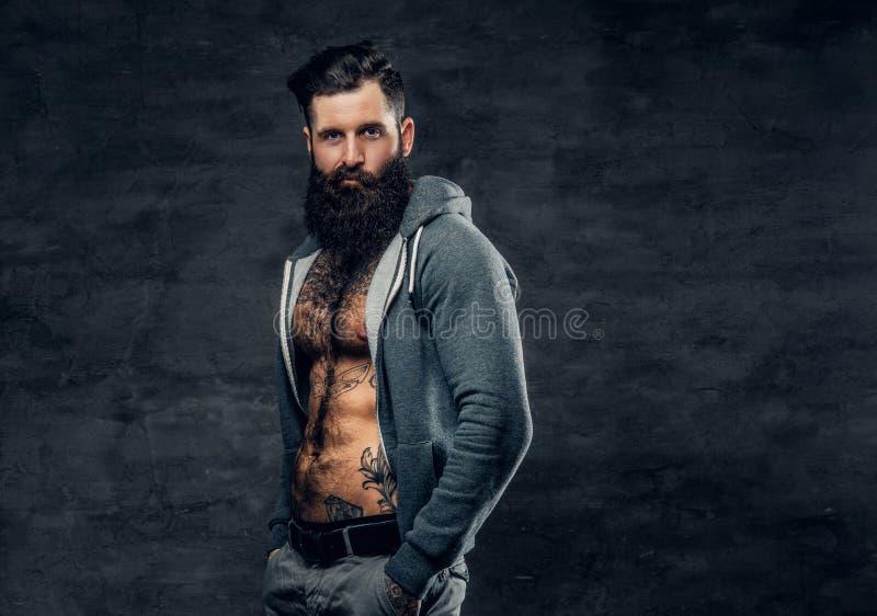 Homem farpado atlético em um hoodie cinzento foto de stock