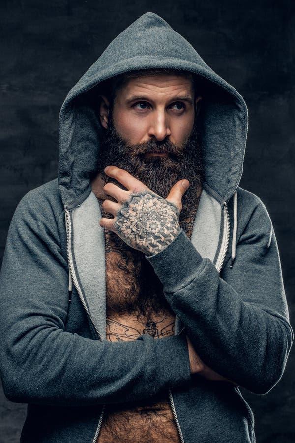 Homem farpado atlético em um hoodie cinzento imagens de stock royalty free