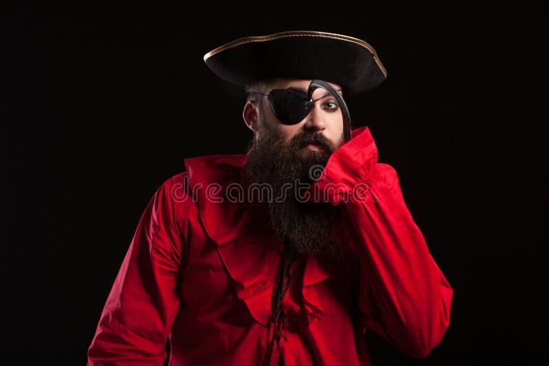 Homem farpado atrativo em um traje do pirata para o carnaval que toca em seu remendo do olho com seu gancho do braço foto de stock