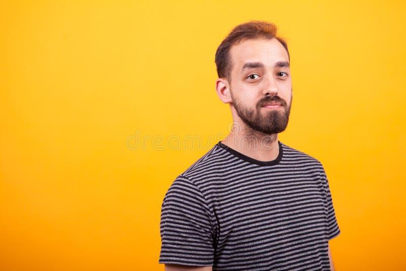 Homem farpado atrativo novo do retrato que veste um t-shirt listrado no fundo amarelo fotos de stock royalty free